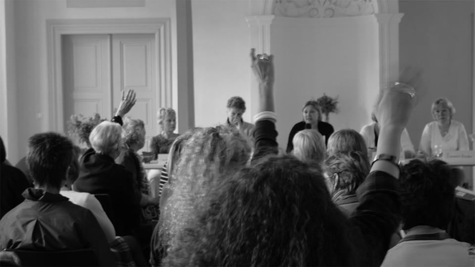 Frauen heben die Hände, um sich an einer Diskussion zu beteiligen