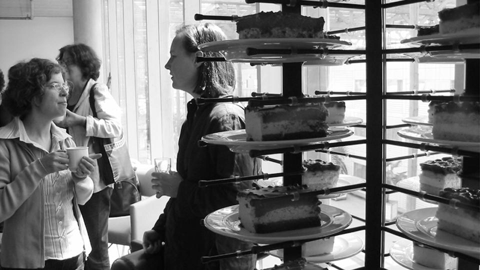 Frauen trinken Kaffee, im Vordergrund einer Etagere mit Torten