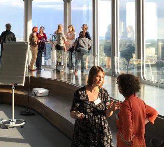 Frauen im Gespräch vor bodentiefen Fenstern im 31. Stockwerk