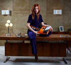 Rothaarige Frau sitzt mit orangefarbener Schreibmaschine auf dem Knie auf Schreibtischkante im 70ies Style