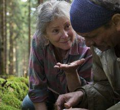 Eine alte Frau kniet im Wald und zeigt einem Mann ein Käfer auf ihrer Hand