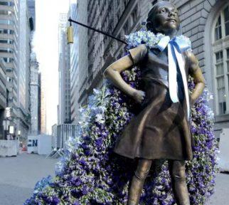 Blumencape für die Statue Fearless Girl vor der Börse von New York