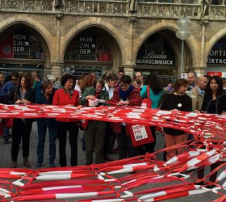 Frauen weben aus rot-weissem Absperrband ein Netz zum Equal-Pay-Day vor dem Münchener Rathaus