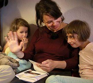 Eine Mutter schaut mit ihren zwei kleinen Töchtern Fotos an