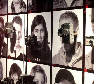 Fotowand mit Portraits von Frauen und Männern mit Fotoapparaten vor der Nase
