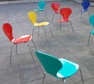 Sechs bunte Stühle stehen herum