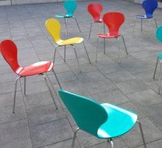 Sechs bunte Stühle stehen wild durcheinander herum