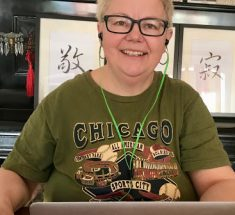 Frau im grünen T-Shirt sitzt vor ihrem Laptop und lächelt in die Kamera