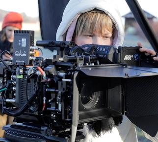 Hinter einer großen Filmkamera steht Nadja Krüger beim Filmen von Amygdala