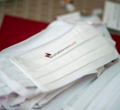 Weiße Gesichtsmasken mit der Aufschrift Journalistinnenbund liegen auf einem Tisch.