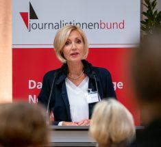 """Petra Gerster steht vor einem rot-weißen Aufsteller mit der Aufschrift """"Journalistinnenbund"""""""
