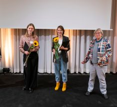 Vier Frauen stehen auf der Bühne, drei halten eine Sonnenblume in der Hand