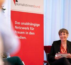"""Eine Frau - die Moderatorin Angelika Knop - sitzt neben einem rot-weißen Aufsteller mit dem Text: """"Journalistinnenbund - Das unabhängige Netzwerk für Frauen in den Medien."""