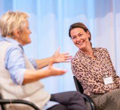 Zwei Frauen auf der Bühne. Renate Künast breitet die Arme aus. Anja Reschke lacht.