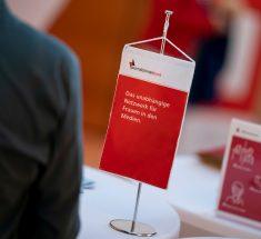 """Ein rot-weißer Wimpel mit der Aufschrift """"Journalistinnenbund - Das unabhängige Netzwerk für Frauen in den Medien"""""""