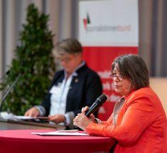 Sabine Zurmühl steht auf der Bühne mit einem Mikrofon in der Hand