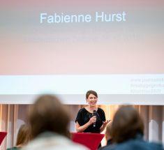Fabienne Hurst steht auf der Bühne mit einem Mikrofon in der Hand