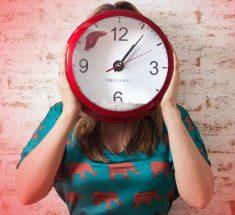 Eine Frau hält eine große Uhr vor ihr Gesicht. Die Zeiger stehen auf 13:07 Uhr