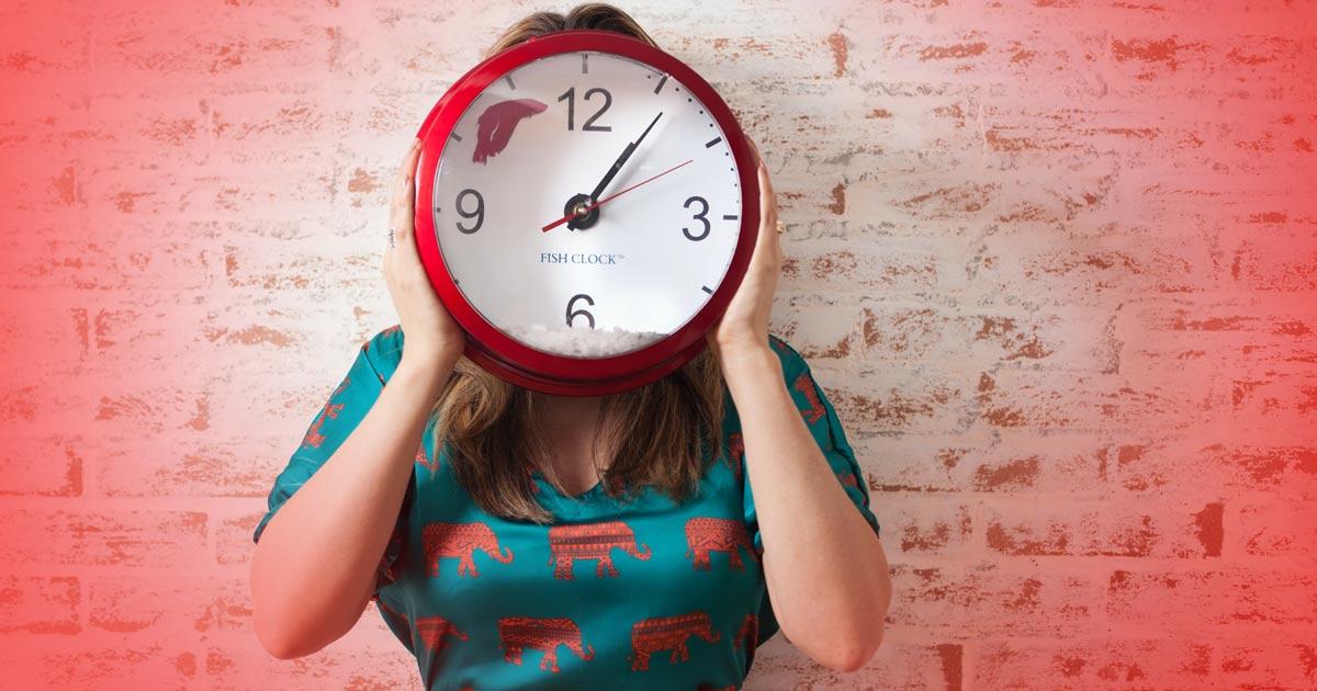 Eine Frau hält eine große runde Uhr vor ihr Gesicht