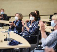 Mehrere Frauen mit Masken sitzen in einem Tagungsraum und applaudieren